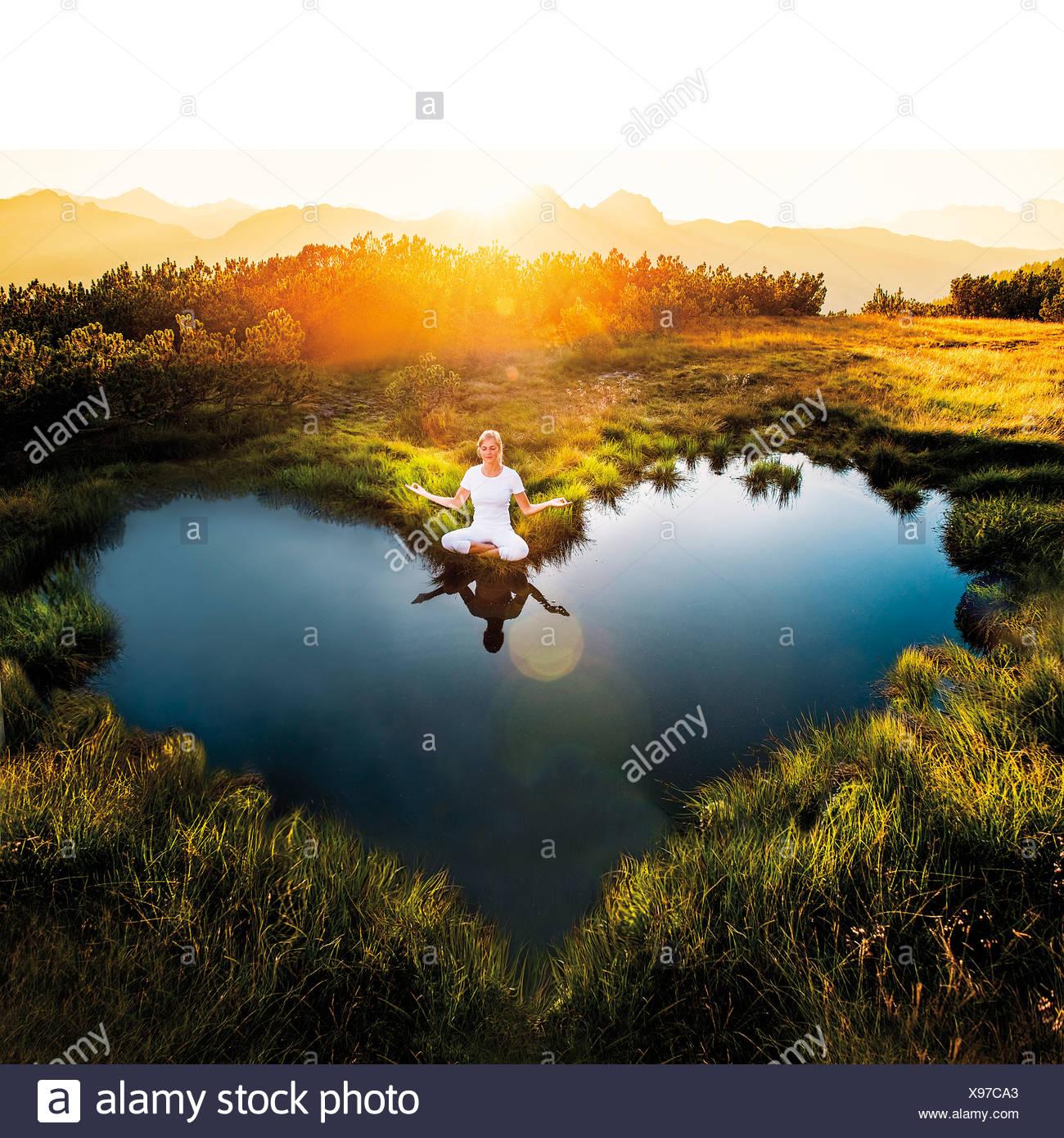 Austria, Salzburgo, Estado Altenmarkt-Zauchensee, mujer meditando en el estanque Imagen De Stock