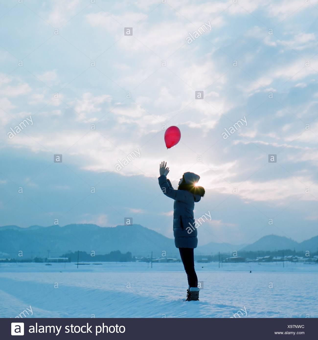 Vista lateral de la chica en ropa de abrigo captura globo rojo estando de pie en el campo nevado Foto de stock
