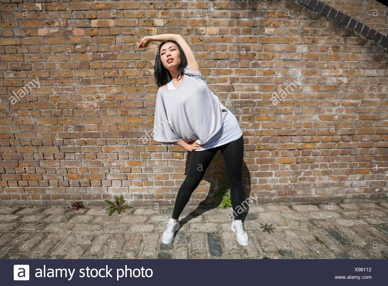 Colocar la longitud completa de la mujer realiza ejercicio de estiramiento contra la pared de ladrillo Imagen De Stock