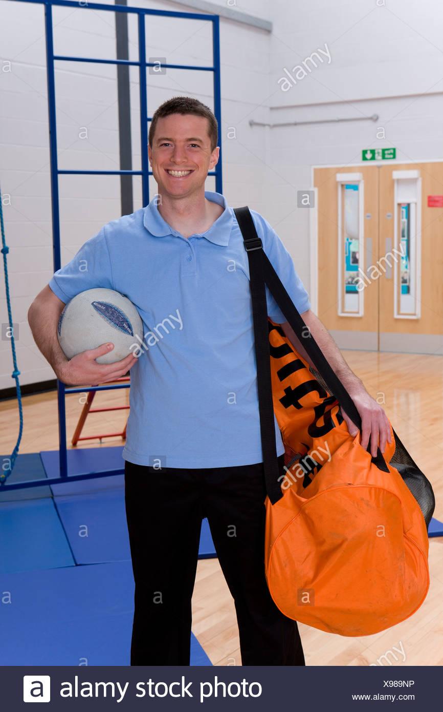 Profesor de gimnasia bolsa de bolas en el gimnasio de la escuela Imagen De Stock