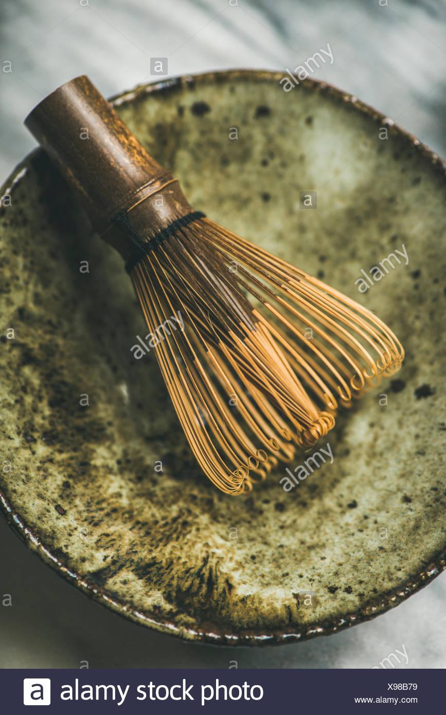 Flat-laicos japoneses de herramientas para la preparación de té matcha. matcha en polvo en lata, chasen batidor de bambú, chawan bowl sobre fondo gris, vista superior Foto de stock