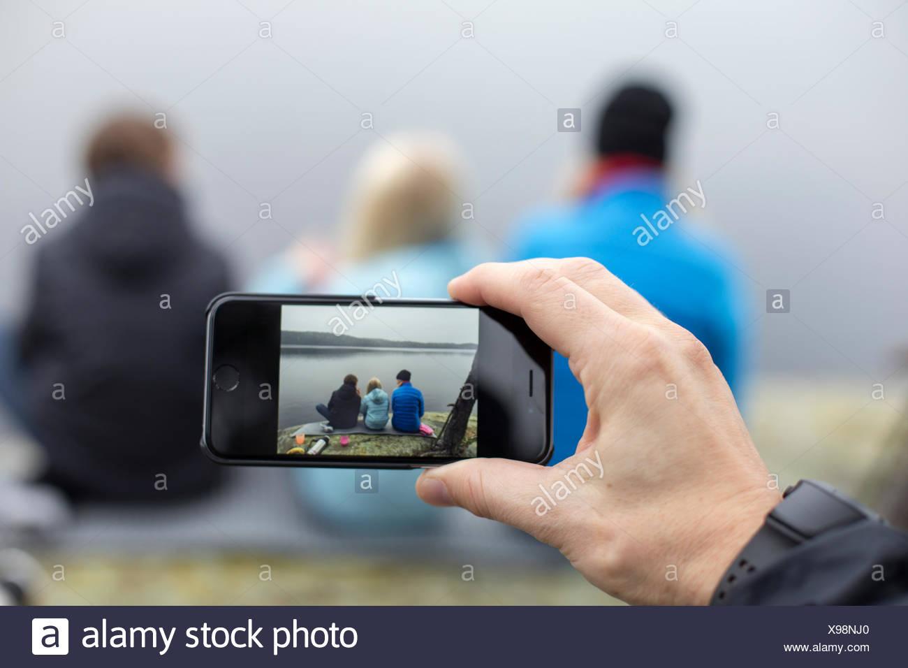 Suecia, Vastergotland, Lerum, Harsjon Harskogen, hombre, tomar la fotografía de una mujer con dos hijos (10-11, 12-13) con el smartphone Foto de stock