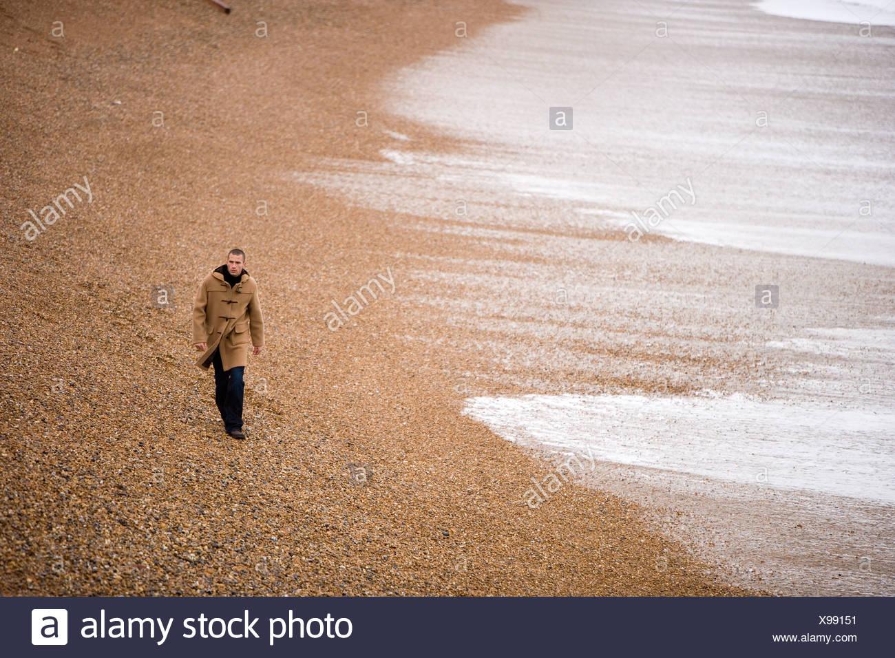 Hombre de duffle coat caminando por la playa de Brighton, REINO UNIDO Imagen De Stock