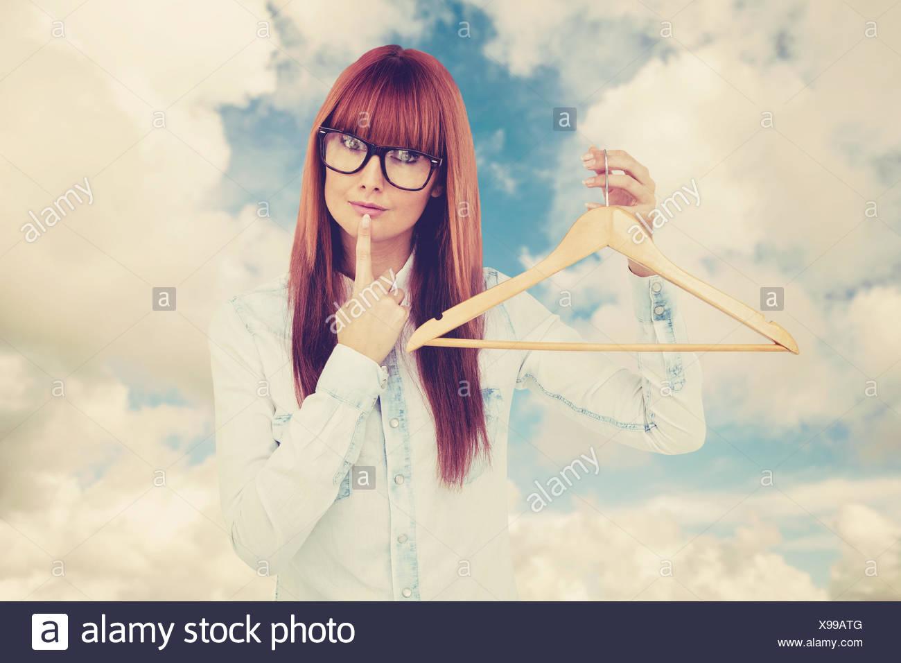 Imagen compuesta de sonriente hipster mujer sosteniendo un perchero Foto de stock