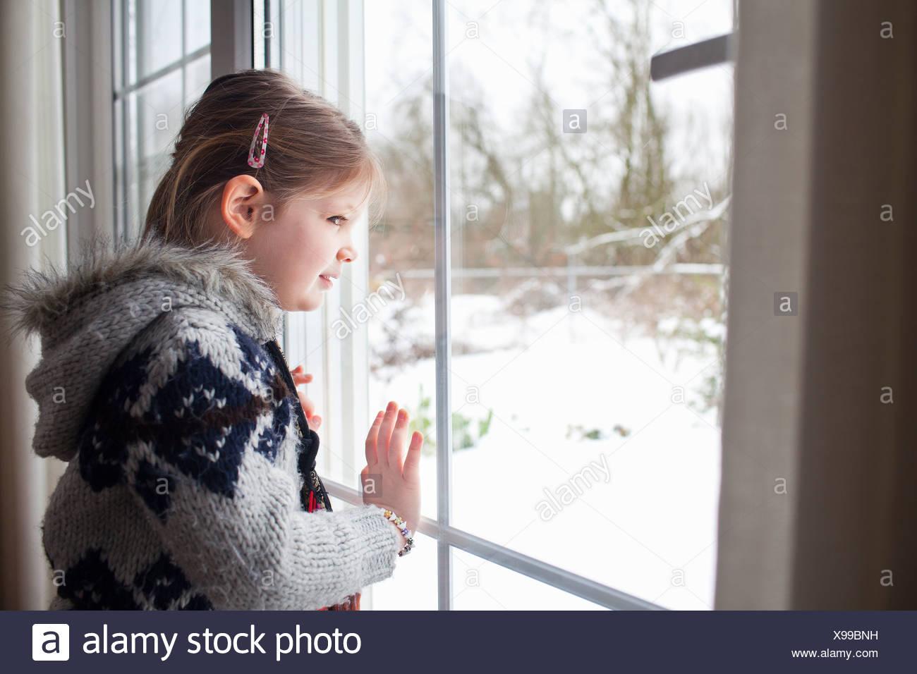 Niña mirando por la ventana al jardín de nieve Imagen De Stock