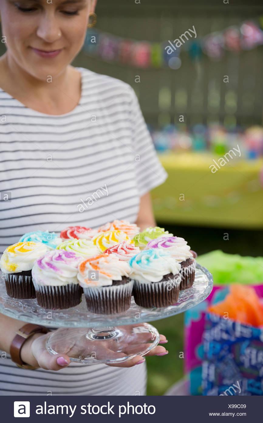 Mujer sosteniendo pastelitos en cake stand Imagen De Stock