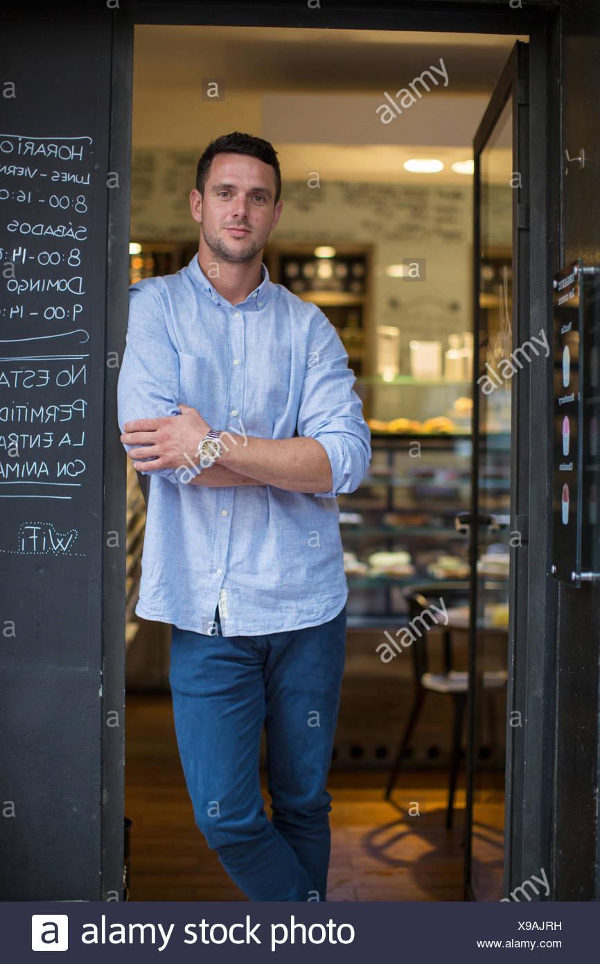 Retrato de mediados adulto macho cafe propietario inclinada contra cafe umbral Imagen De Stock