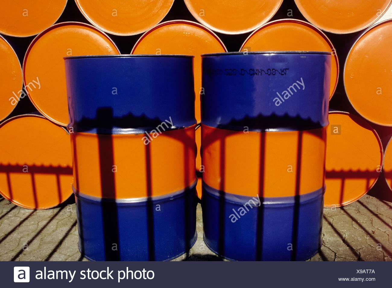 Dos bidones de aceite vertical pintado de dos colores de pie en frente de una fila de tambores de aceite apiladas Foto de stock