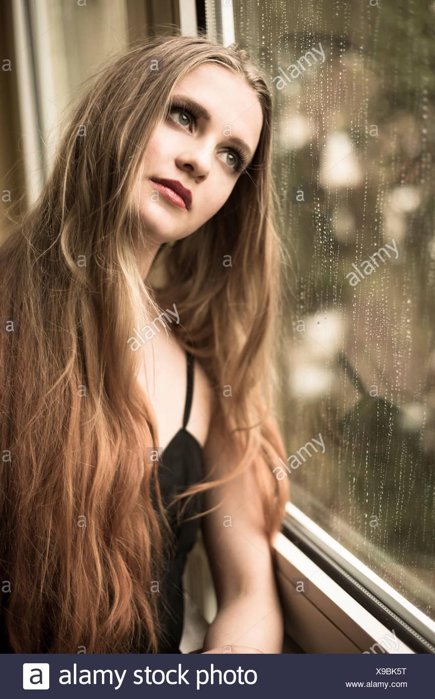 Retrato de mujer joven mirando a través de la ventana Imagen De Stock
