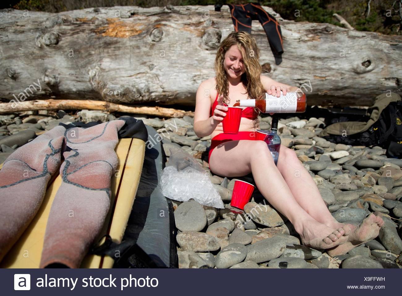 Mujer joven sentado en la playa rocosa, verter la bebida, Short Sands Beach, Oregón, EE.UU. Imagen De Stock