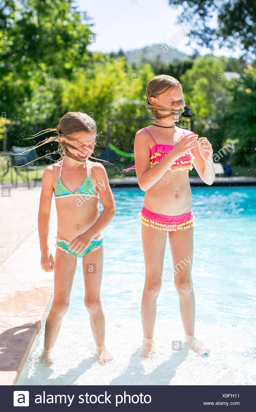 Dos hermanas agitando el cabello mojado por la piscina exterior Imagen De Stock