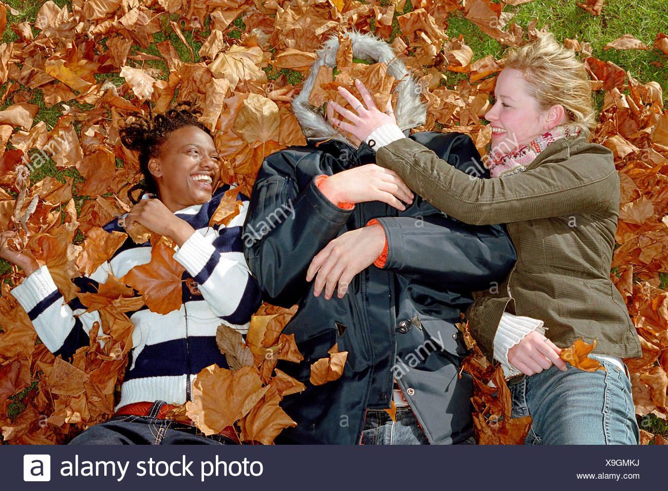 Personas jugando en hojas Foto de stock