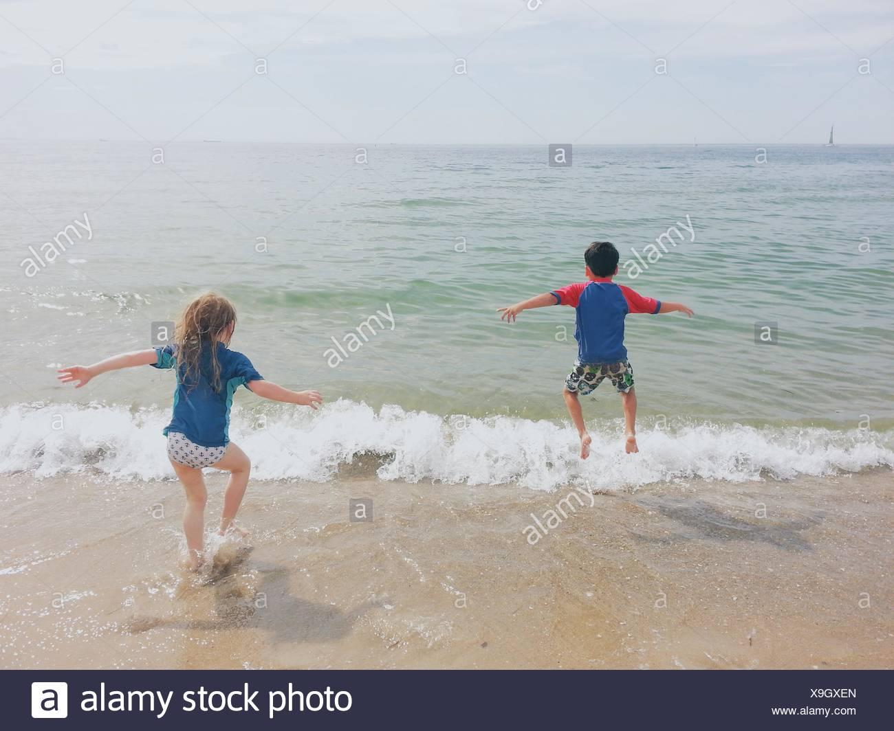 Chico y chica corriendo en el océano Imagen De Stock
