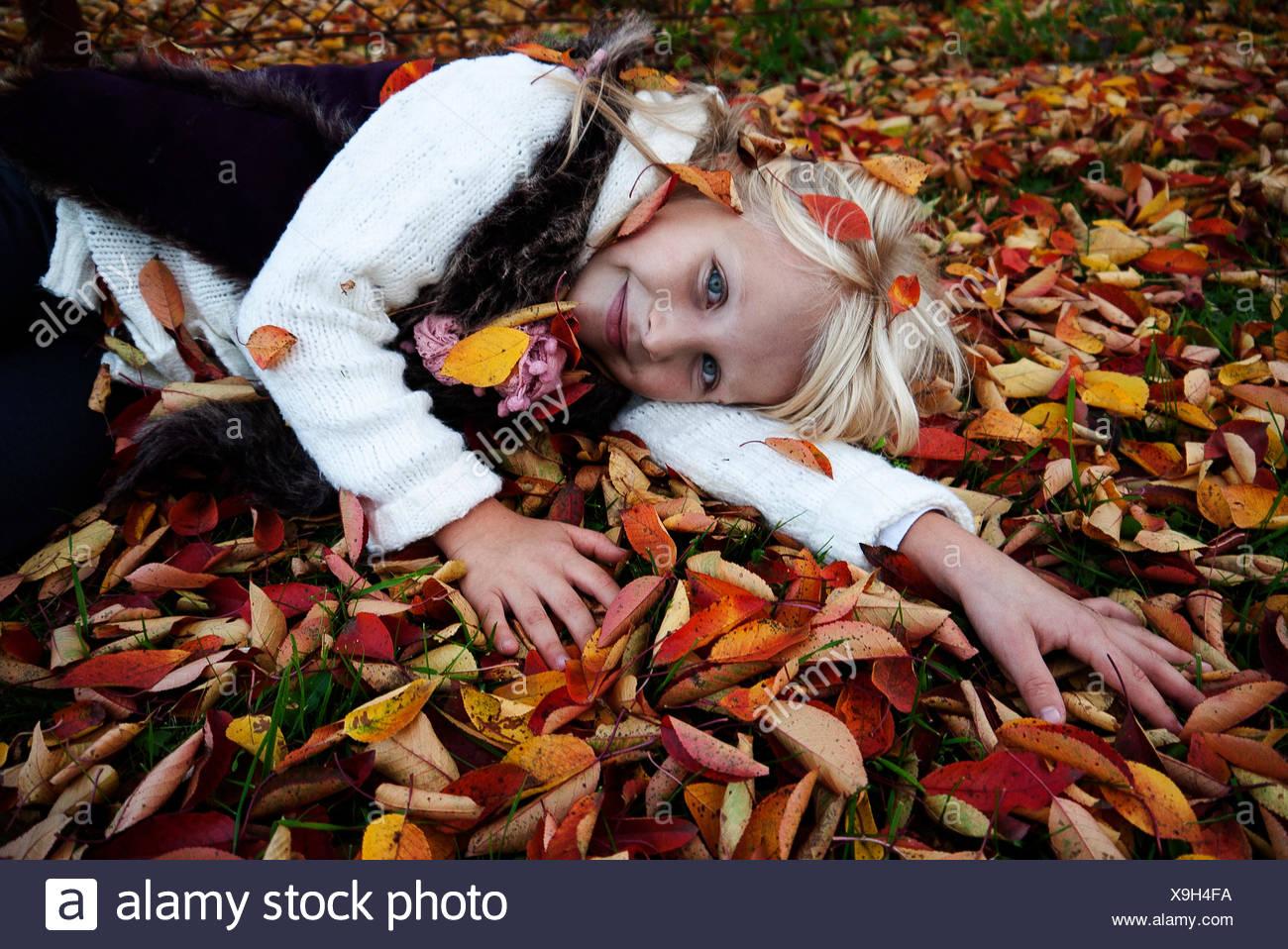 Chica (6-7) tumbado sobre hojas de otoño Imagen De Stock