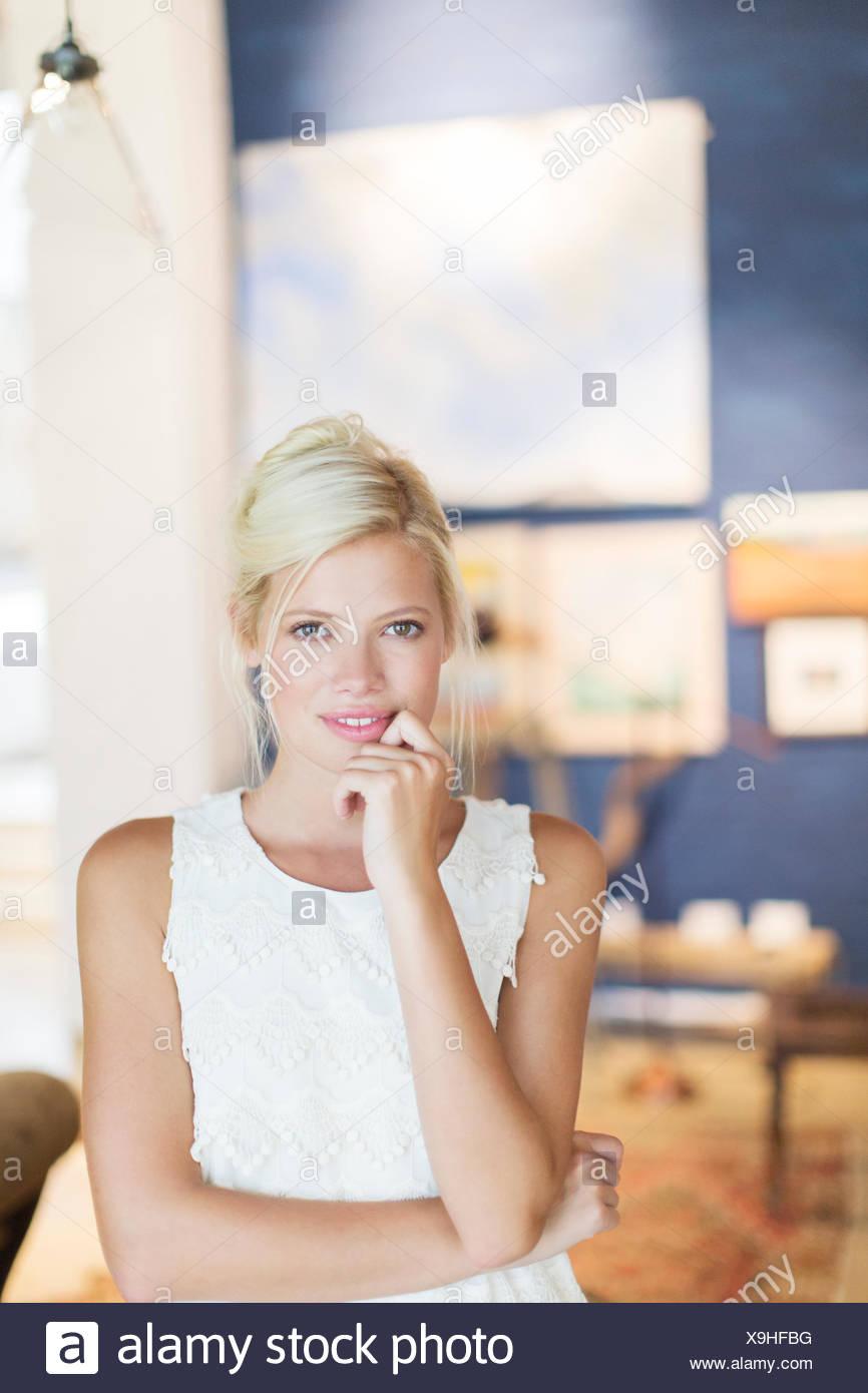 Mujer sosteniendo su barbilla en la mano Imagen De Stock