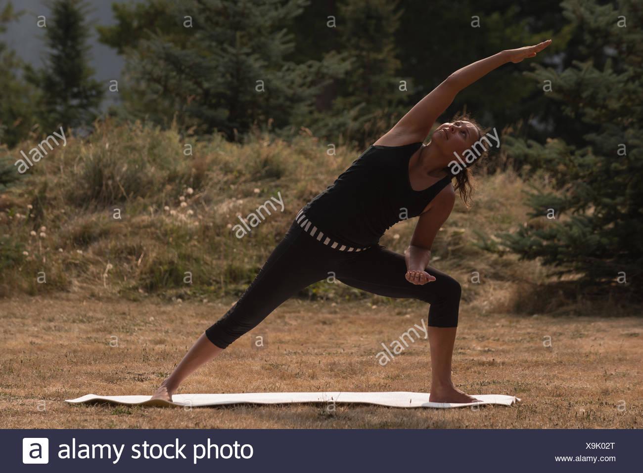 Colocar mujer realizar ejercicio de estiramiento en un terreno abierto Imagen De Stock