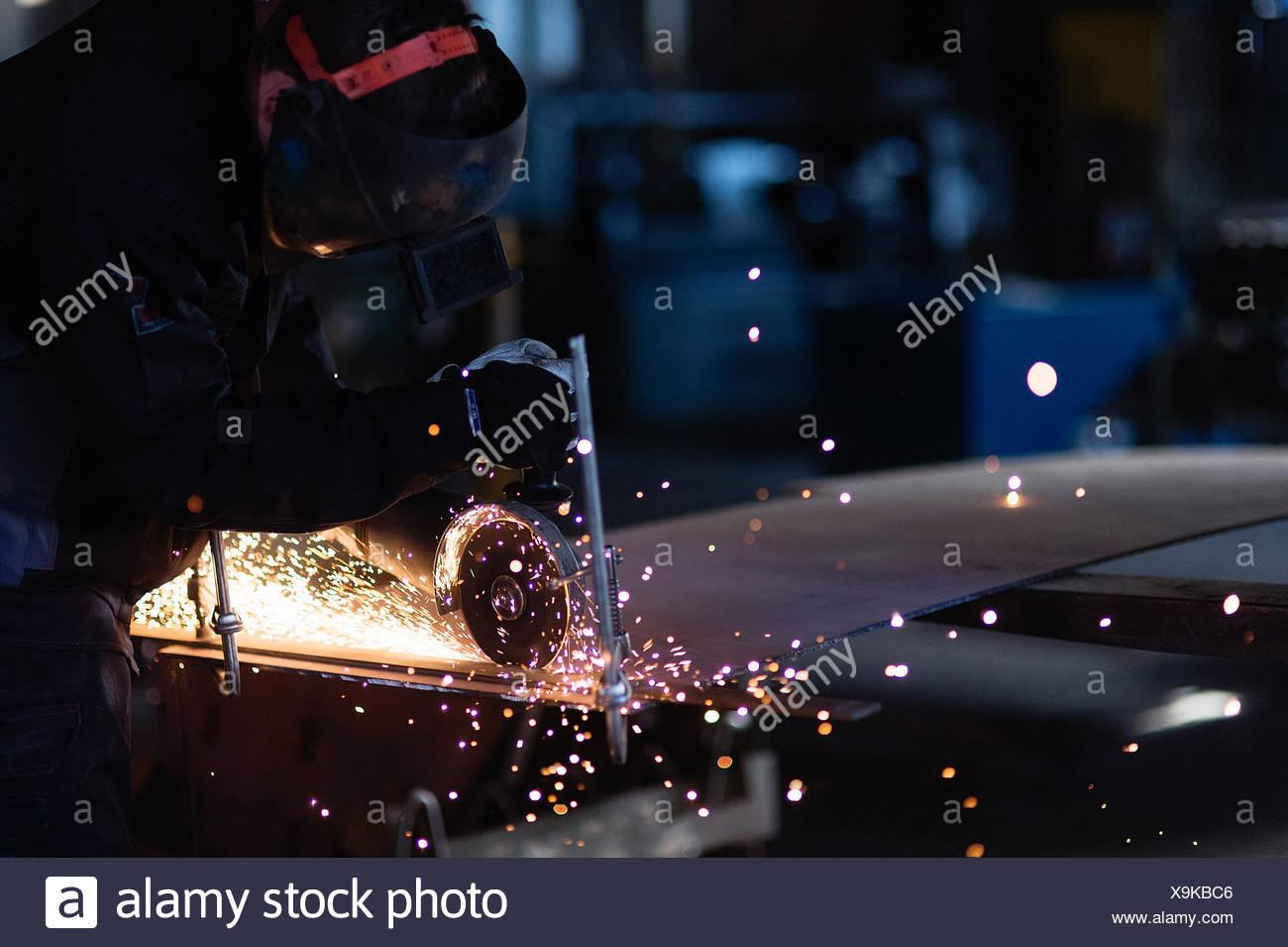 Suecia, joven cortar metal en el taller Imagen De Stock