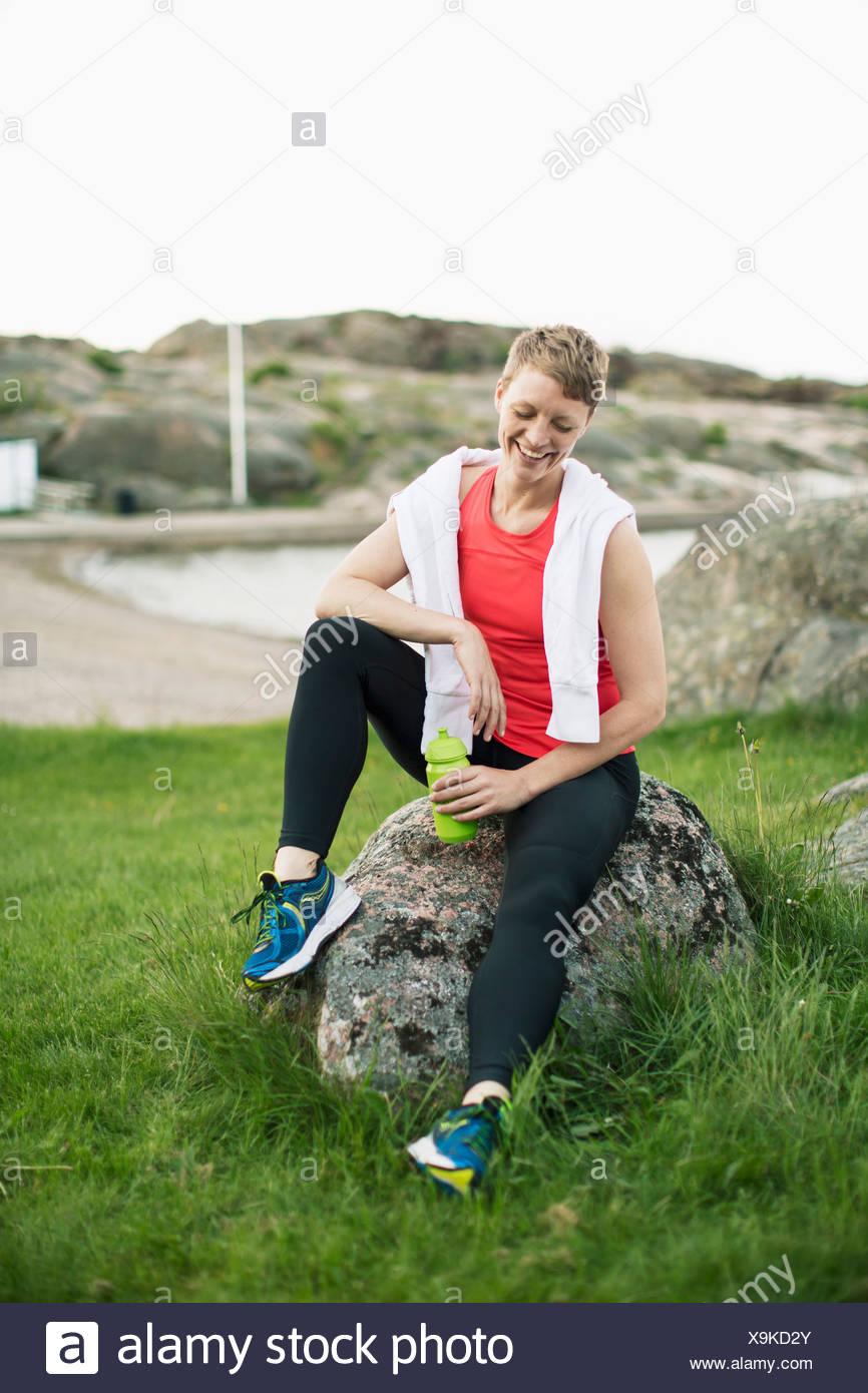 Feliz mujer en ropa deportiva con la botella de agua y una toalla relajándose en roca Imagen De Stock
