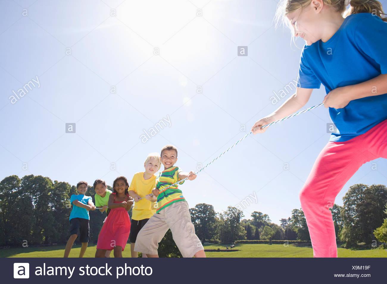 Un grupo de niños jugando Tug of War en estacionamiento Imagen De Stock