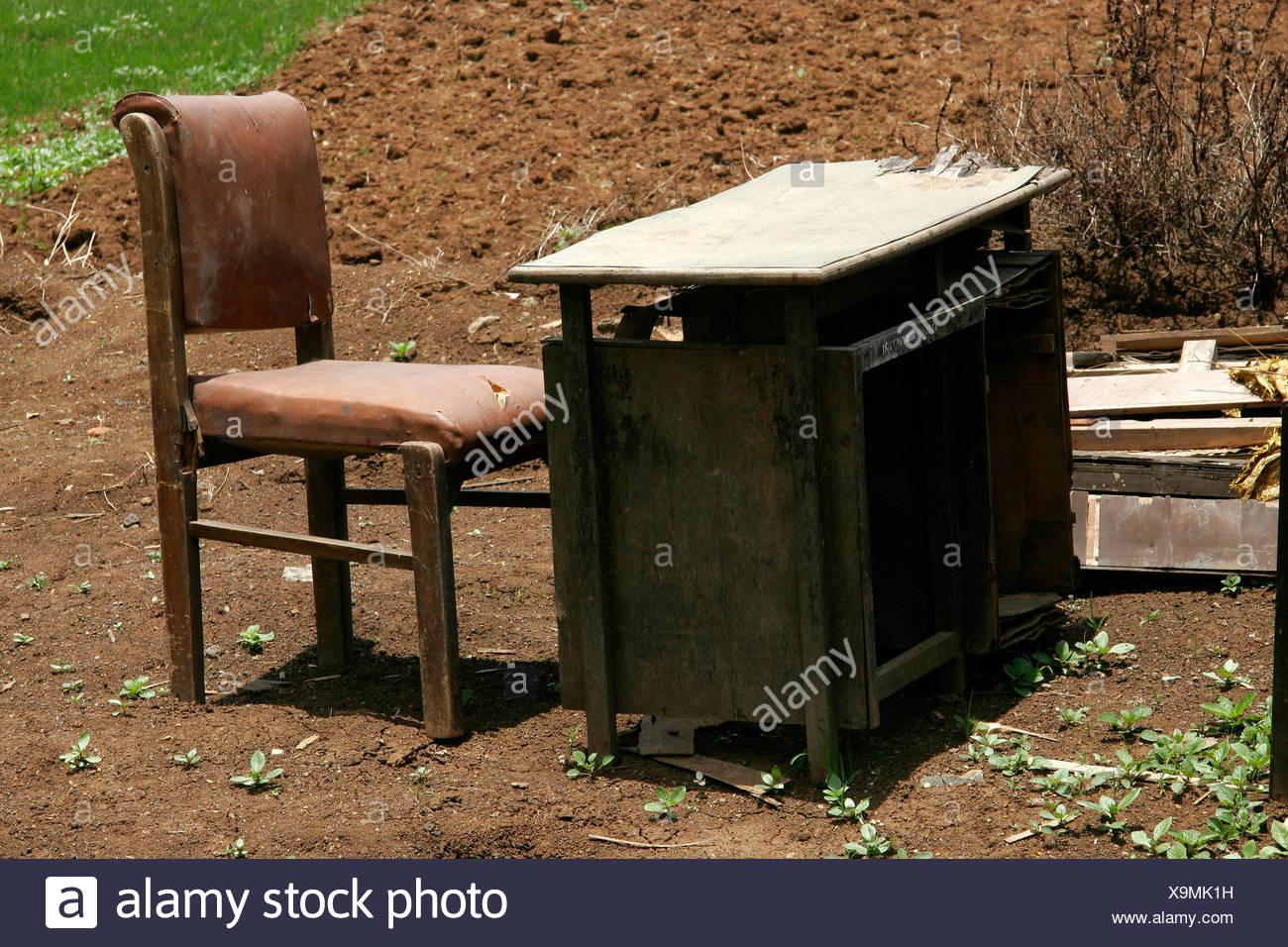 Mesa y silla artificiales en etapa rota dispuestos en la naturaleza Foto de stock