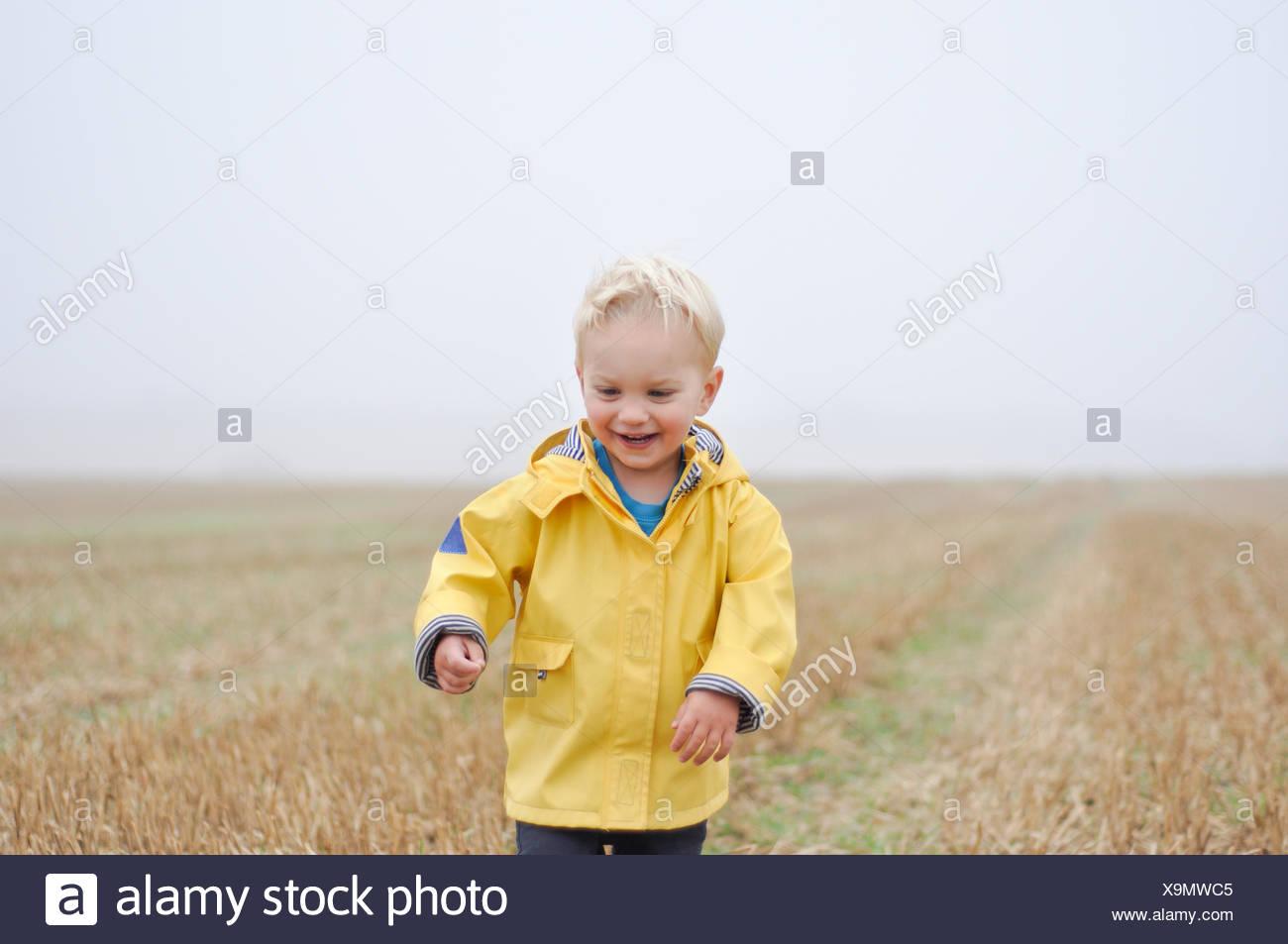 Muchacho en una capa de lluvia de pie en un campo de trigo, Inglaterra, Reino Unido. Imagen De Stock