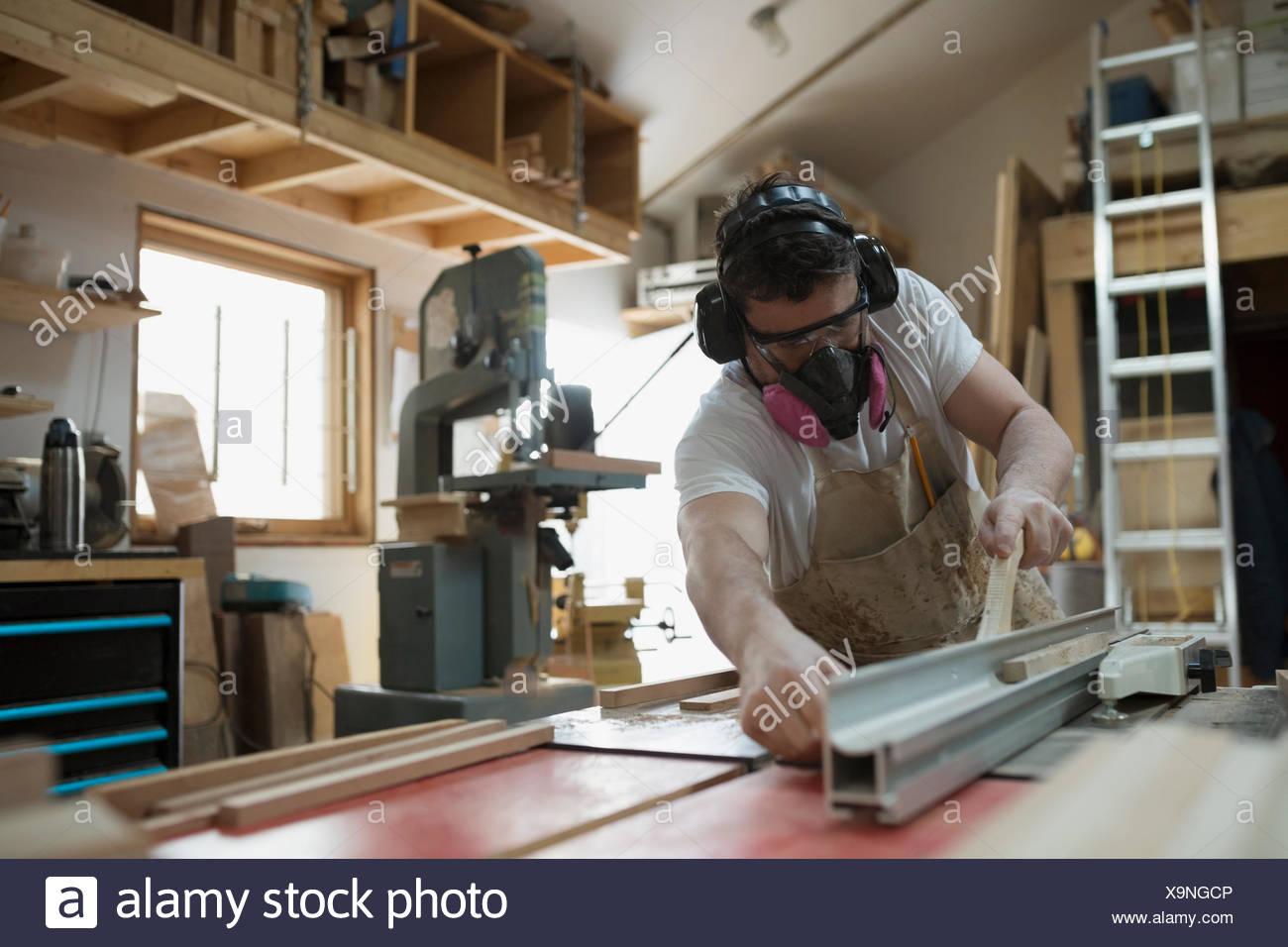 Carpenter vistiendo máscara protectora en el taller Imagen De Stock