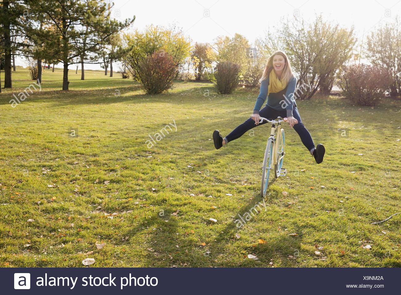 Juguetón mujer bicicleta Equitación en un soleado día de otoño park Imagen De Stock