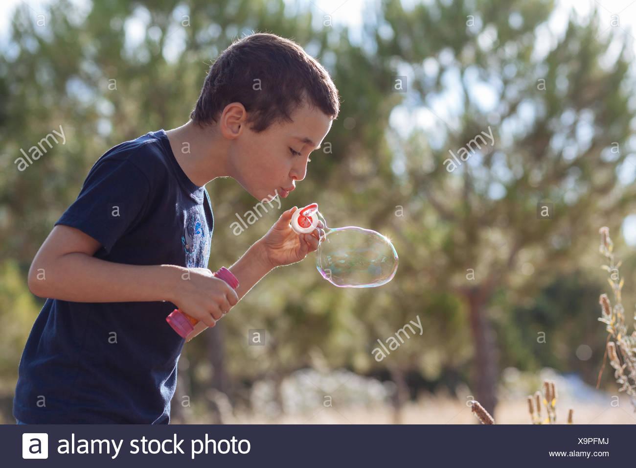 Muchacho soplando burbujas sobre las plantas. Foto de stock