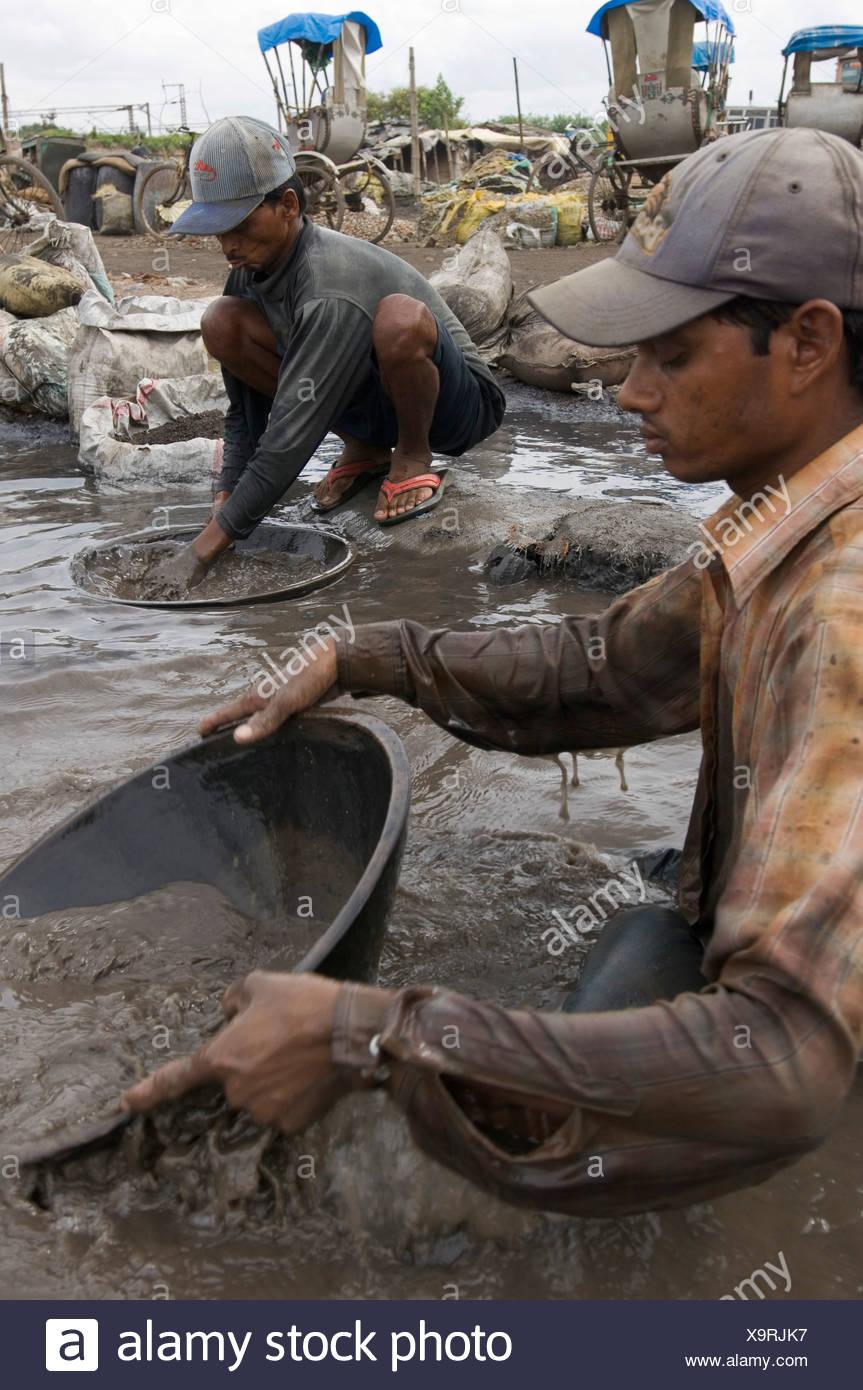 Muchos habitantes de tugurios se ganan la vida reciclando residuos industriales, estos trabajadores son venenosos residuos industriales de lavado Imagen De Stock