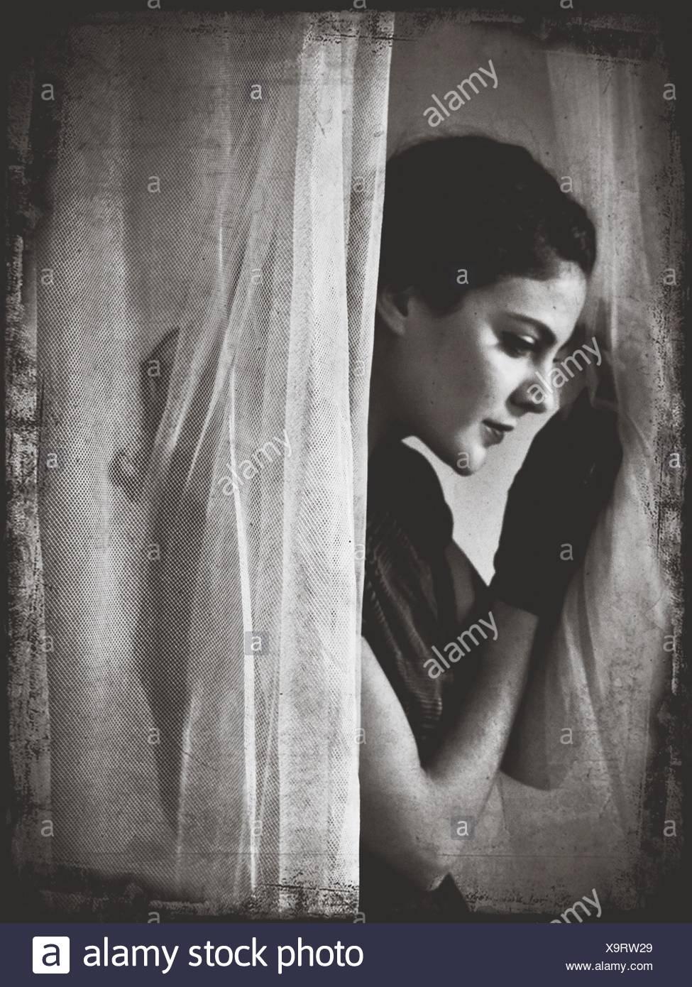 Vista lateral de la joven mujer de pie por cortinas Foto de stock