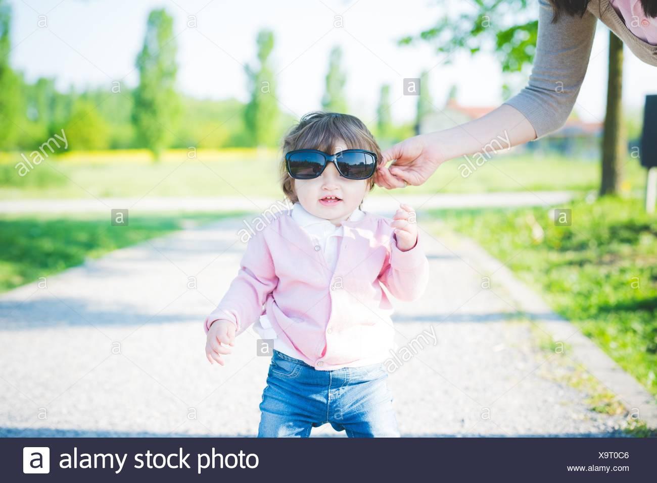 Retrato de niño hembra con gafas de sol en el parque Imagen De Stock