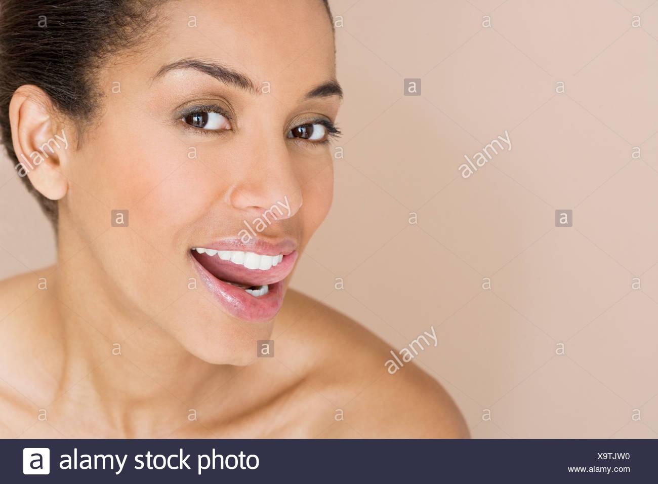 Una mujer ejecutando la lengua a lo largo de los dientes Imagen De Stock
