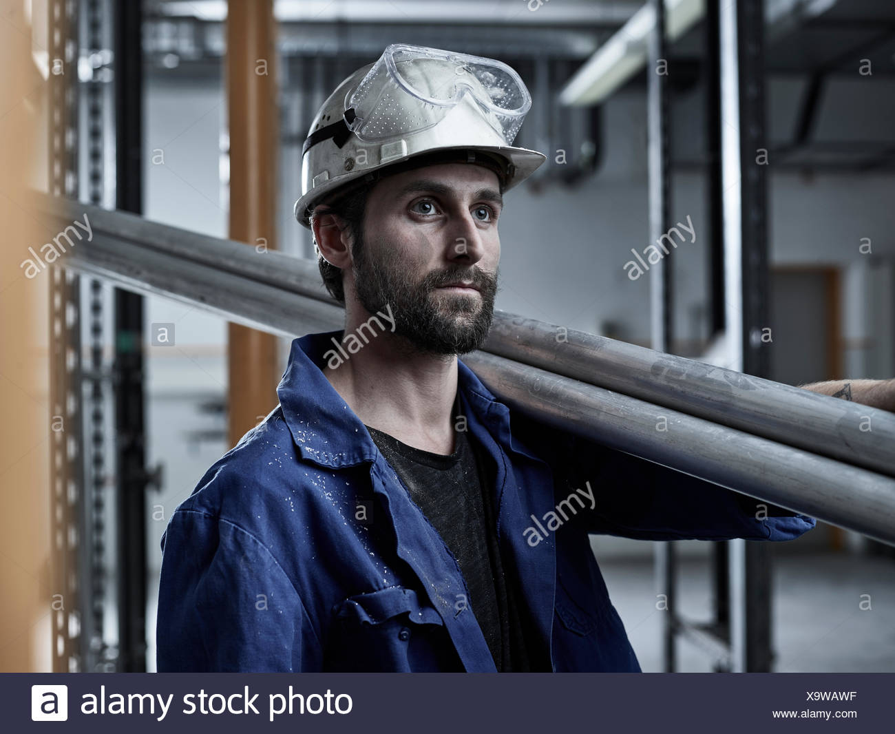 Trabajador mecánico, con cascos y gafas de seguridad llevar tubos en su hombro, Austria Foto de stock