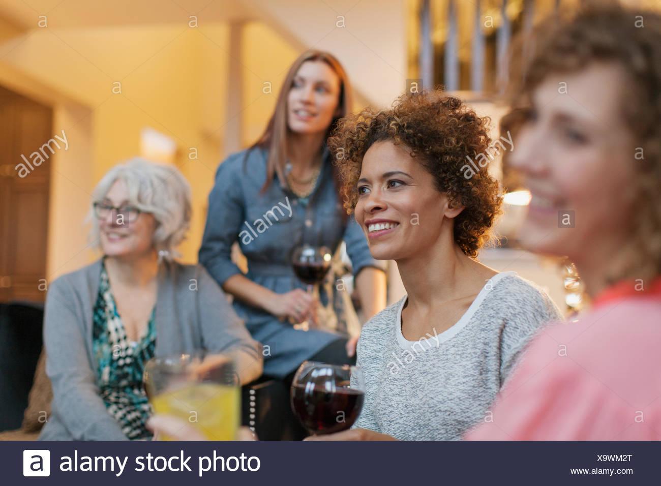Amigas disfrutando de una copa de vino en casa. Imagen De Stock