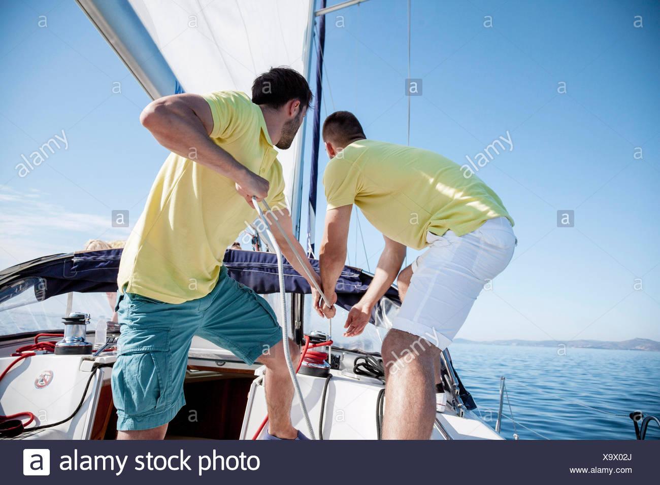 Dos hombres tirando de la cuerda juntos en velero, Mar Adriático Imagen De Stock