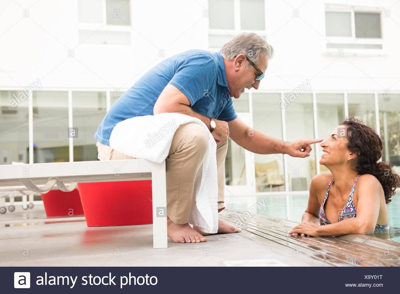 Hombre que toca Senior wifes nariz de piscina. Imagen De Stock