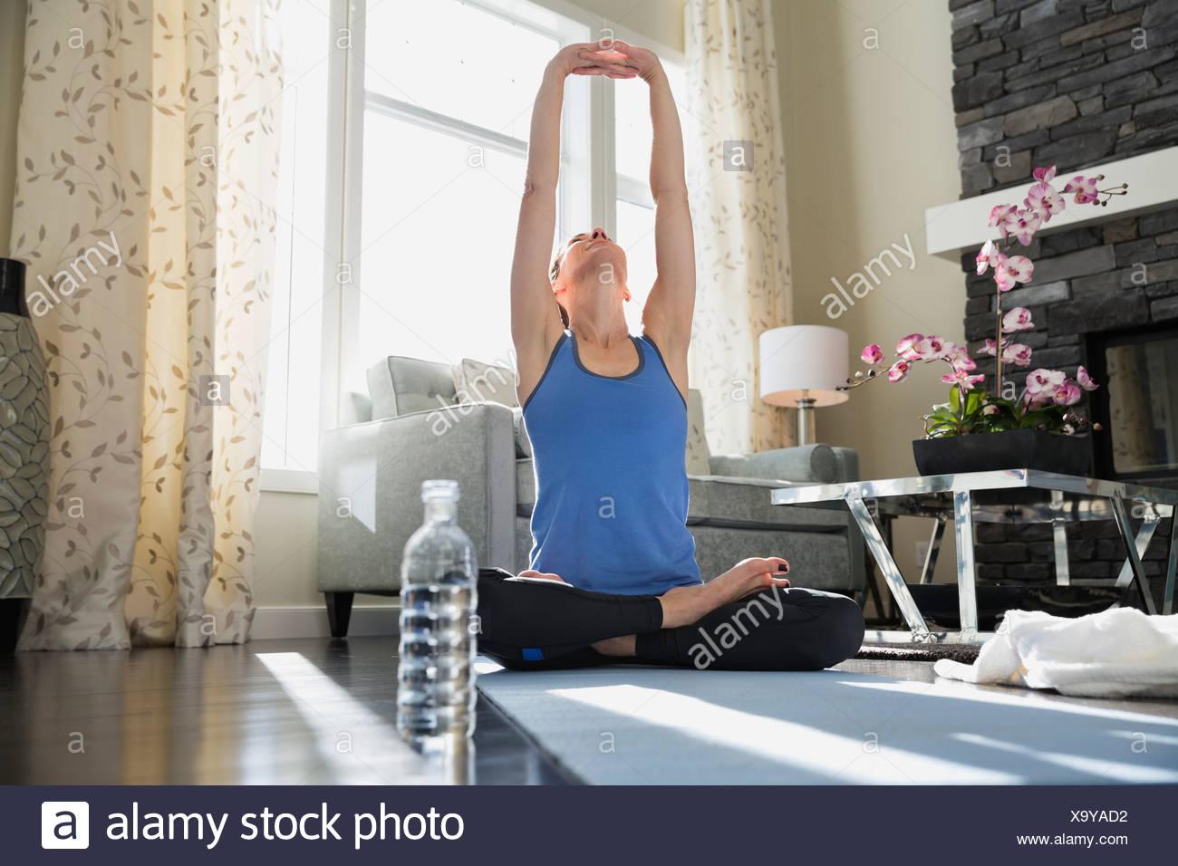 Mujer madura con los brazos levantados haciendo yoga en mat Imagen De Stock