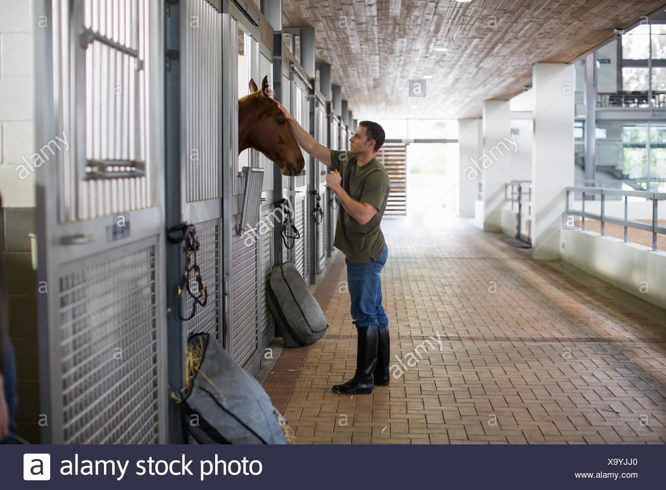Stablehand masculina besándose en los establos de caballos Imagen De Stock