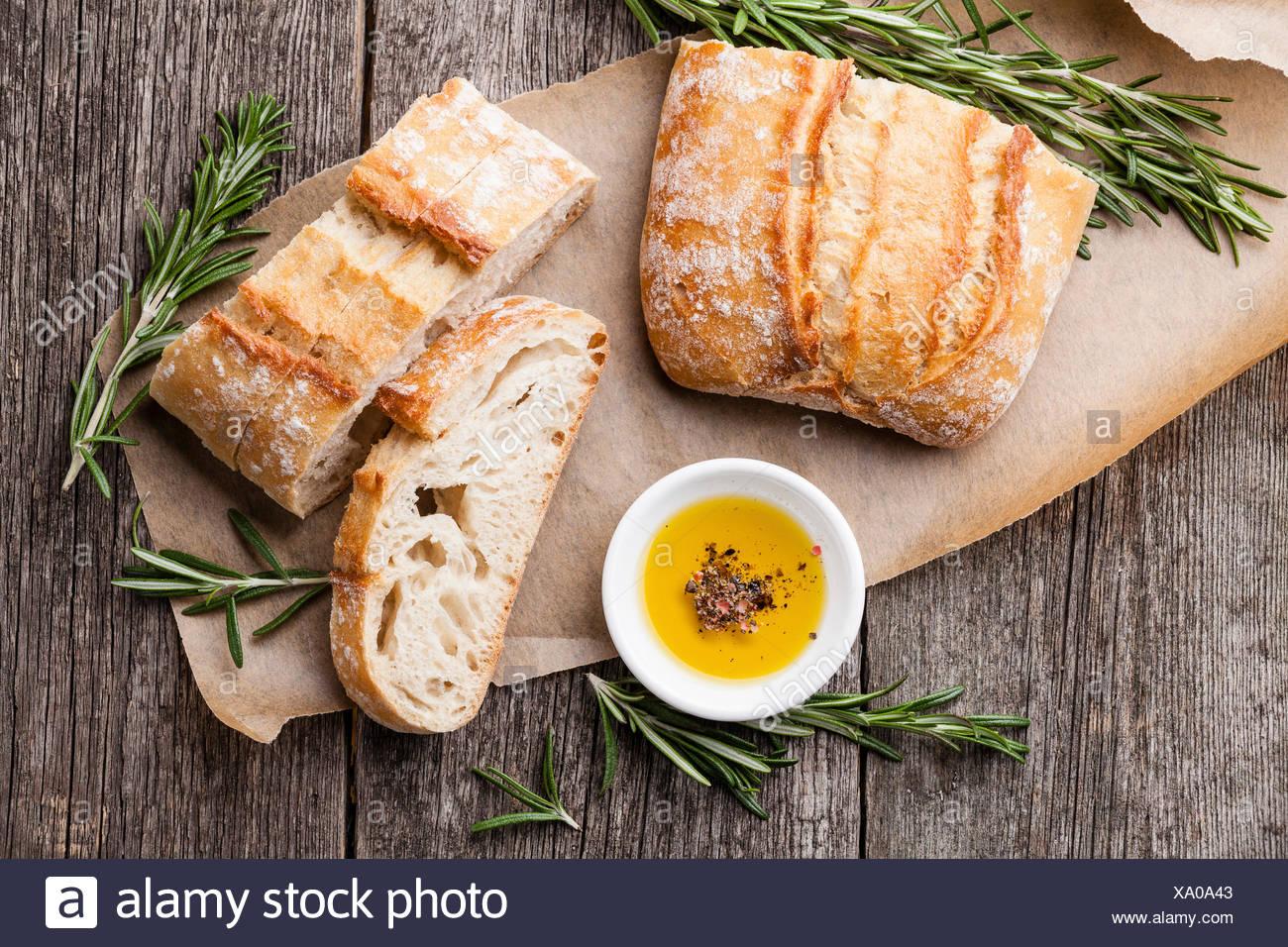 Rebanadas de pan ciabatta y aceite de oliva virgen extra en el fondo de madera Imagen De Stock