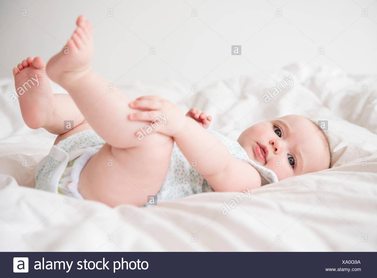 Niña (12-17 meses) acostada en la cama Imagen De Stock