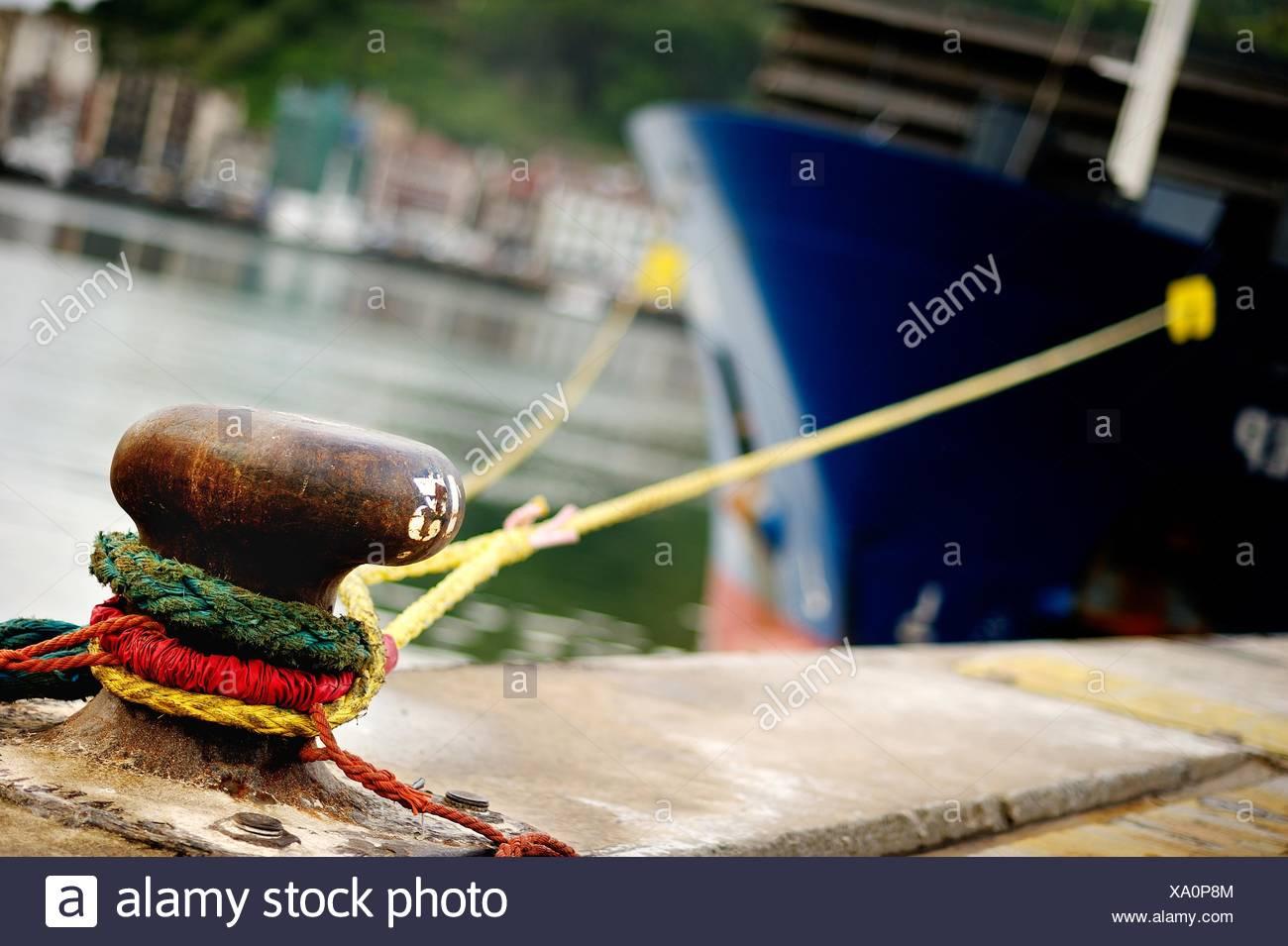Carguero atracado en el puerto de Pasajes en el noray Foto de stock