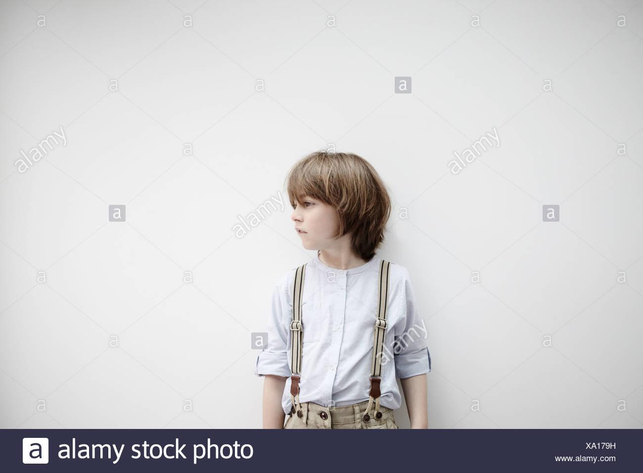 Niño de pie contra la pared blanca Imagen De Stock
