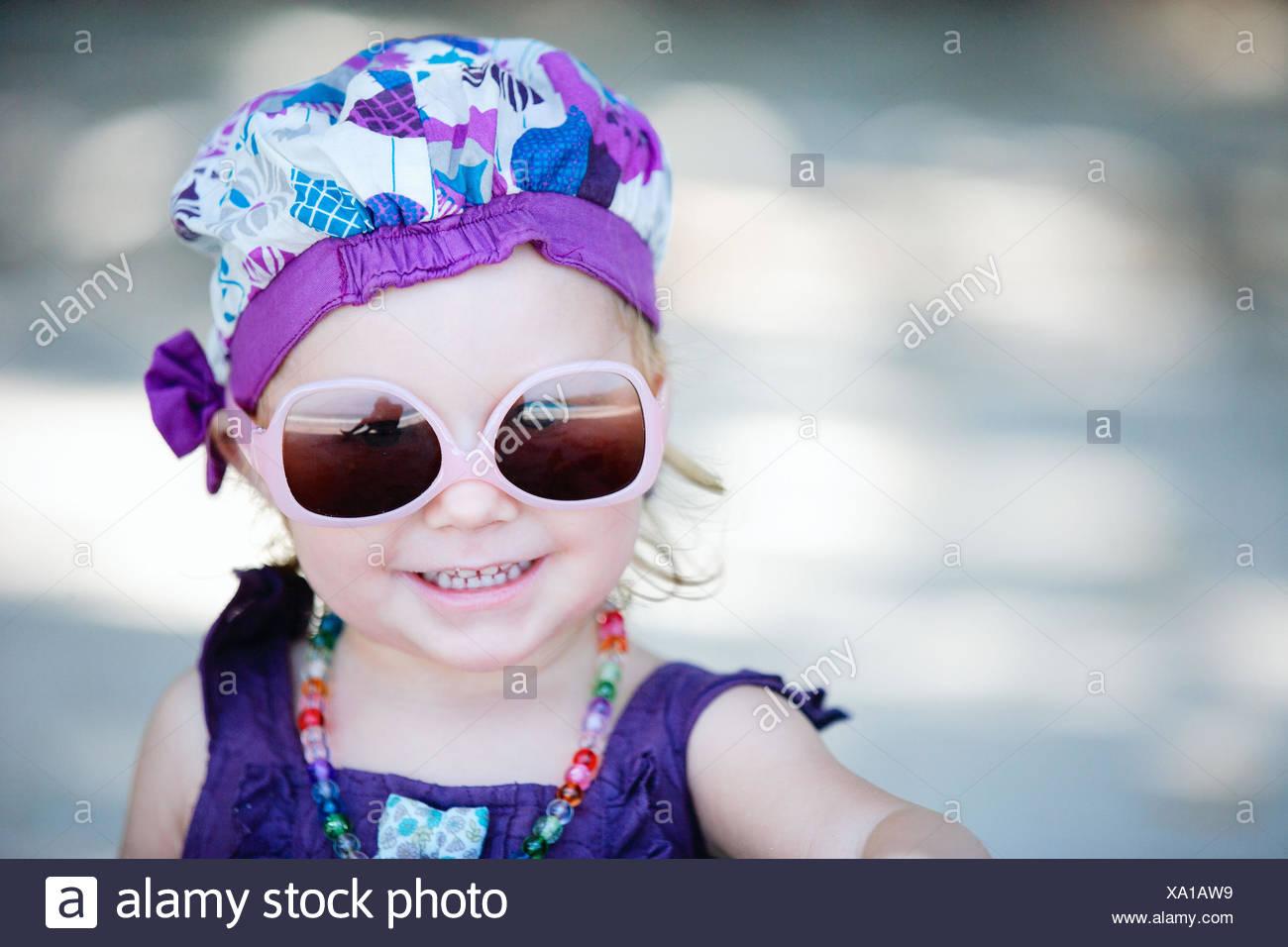 e6bf9e498 Retrato de una niña con gafas de sol y ropa extravagante Imagen De Stock