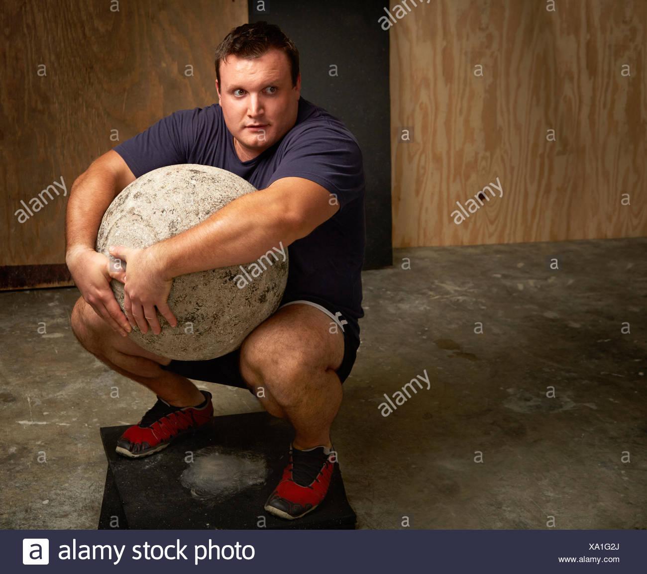 Retrato de macho joven levantador de pesas en cuclillas con atlas ball en el gimnasio Imagen De Stock