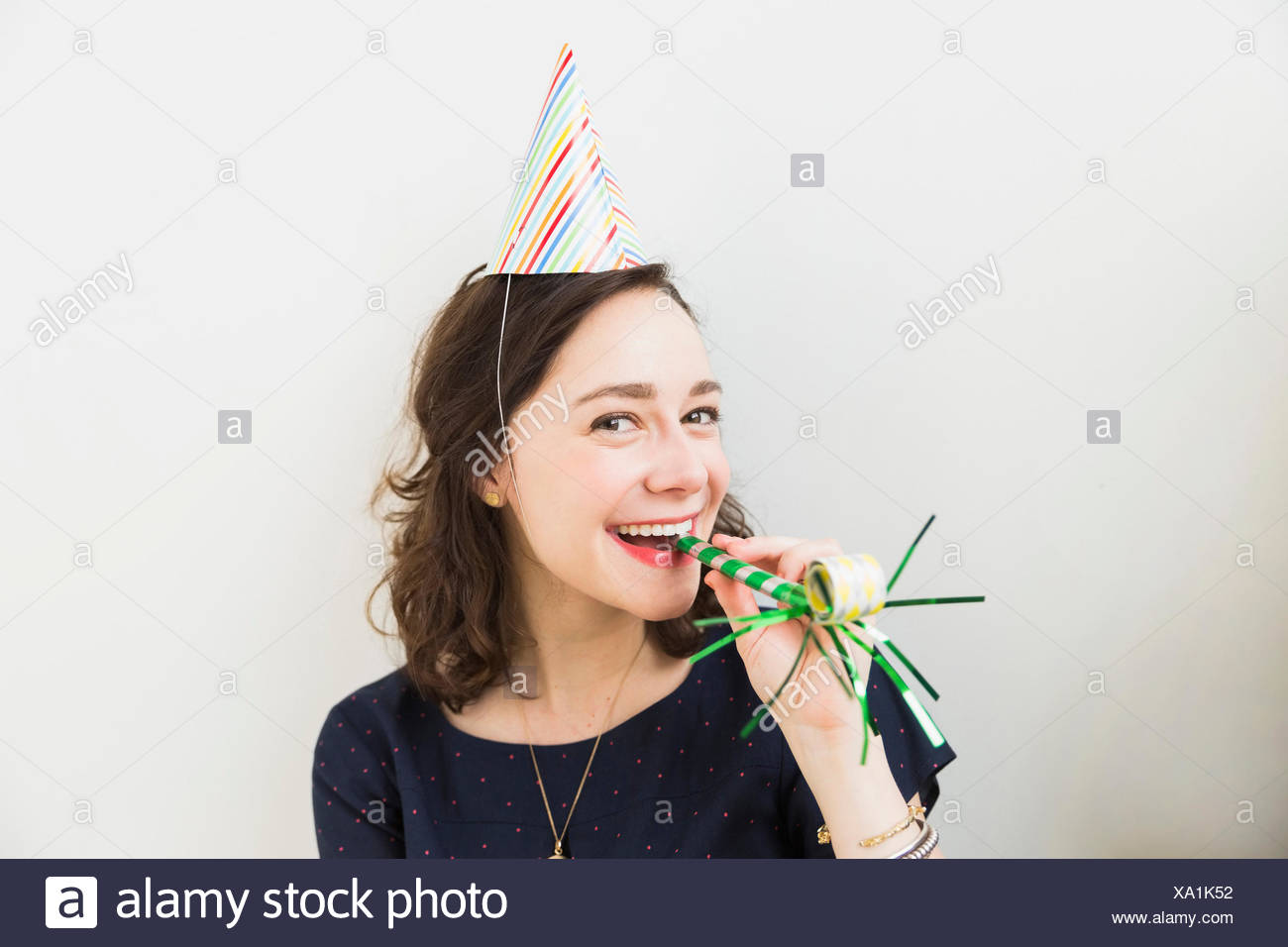 Mujer sonriente con parte del soplador de la bocina Imagen De Stock