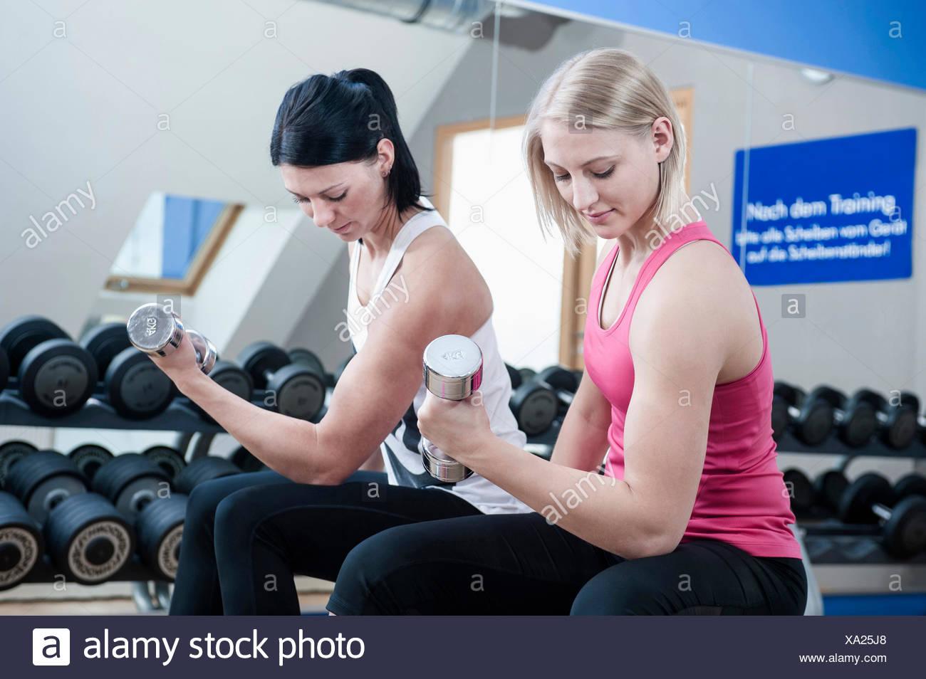Dos mujeres en el gimnasio haciendo pesas Imagen De Stock