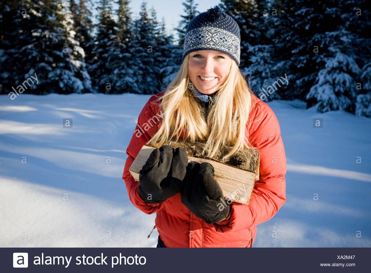 Mujer joven en raquetas de nieve lleva madera cortada cerca de Homer, Alaska durante el invierno. Imagen De Stock