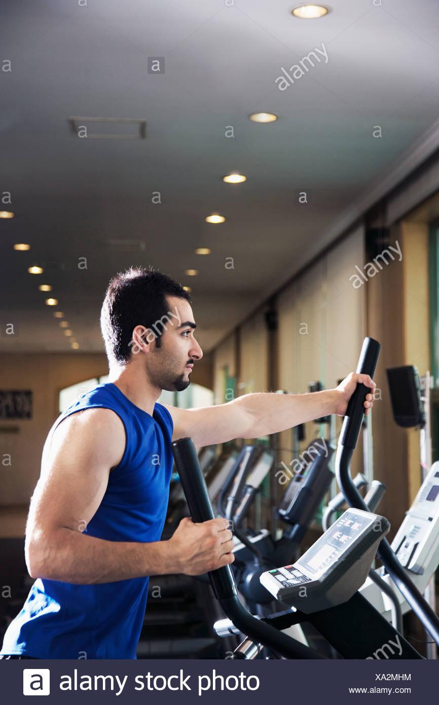 Joven Hombre muscular ejerce sobre un entrenador de cross en el gimnasio. Imagen De Stock