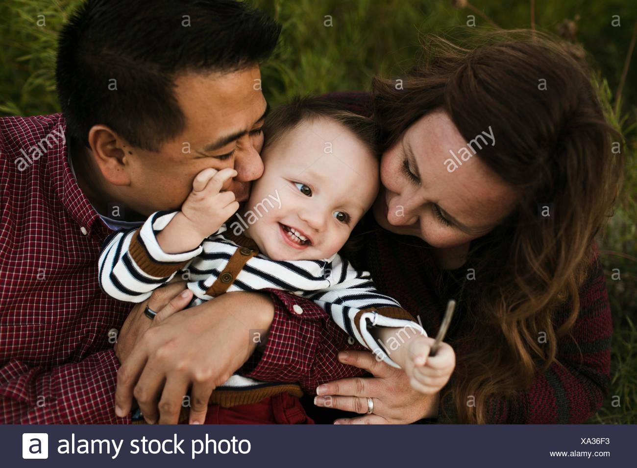 La madre y el padre abrazando sonriente baby boy Imagen De Stock