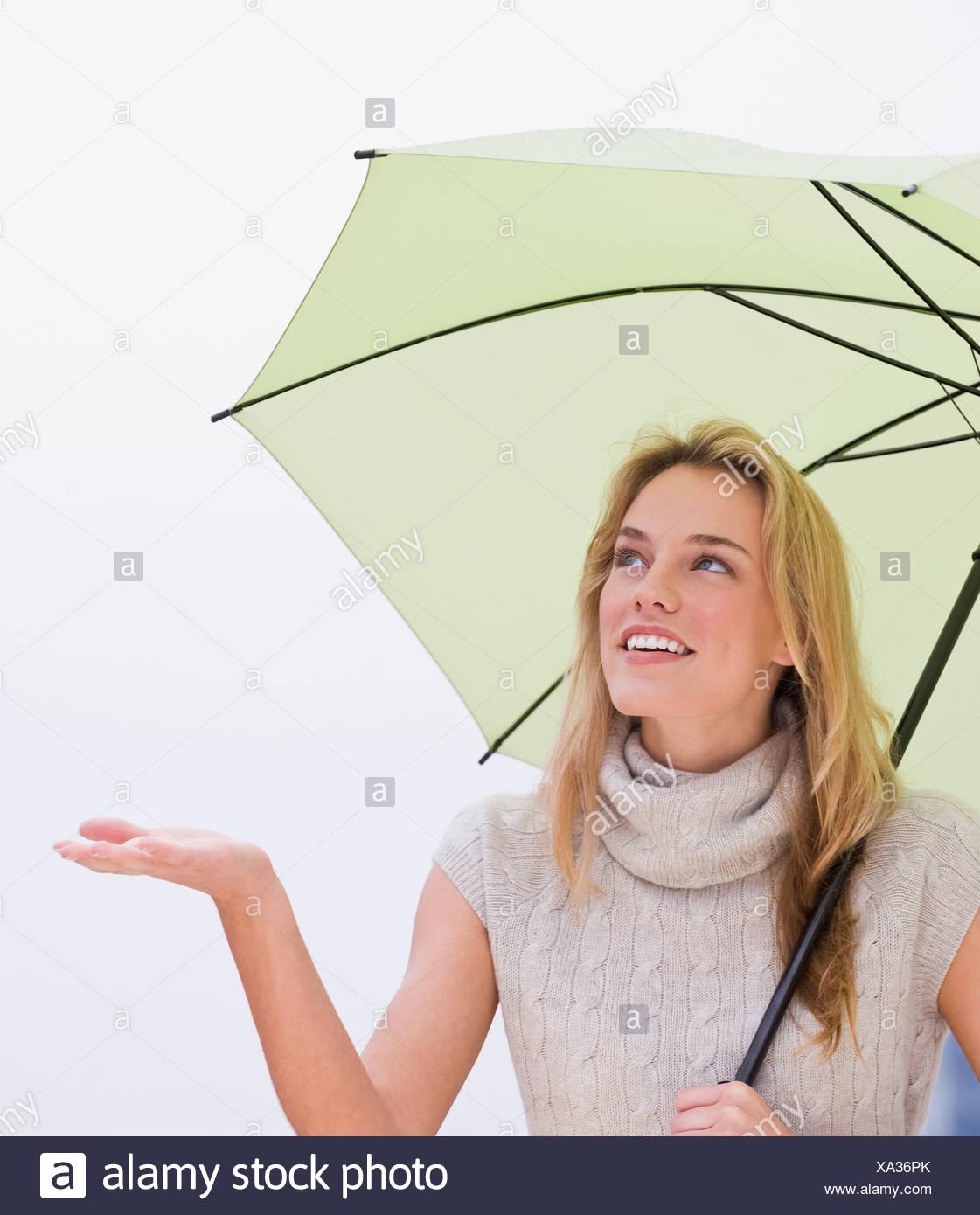 Mujer sosteniendo la mano por debajo de paraguas Foto de stock